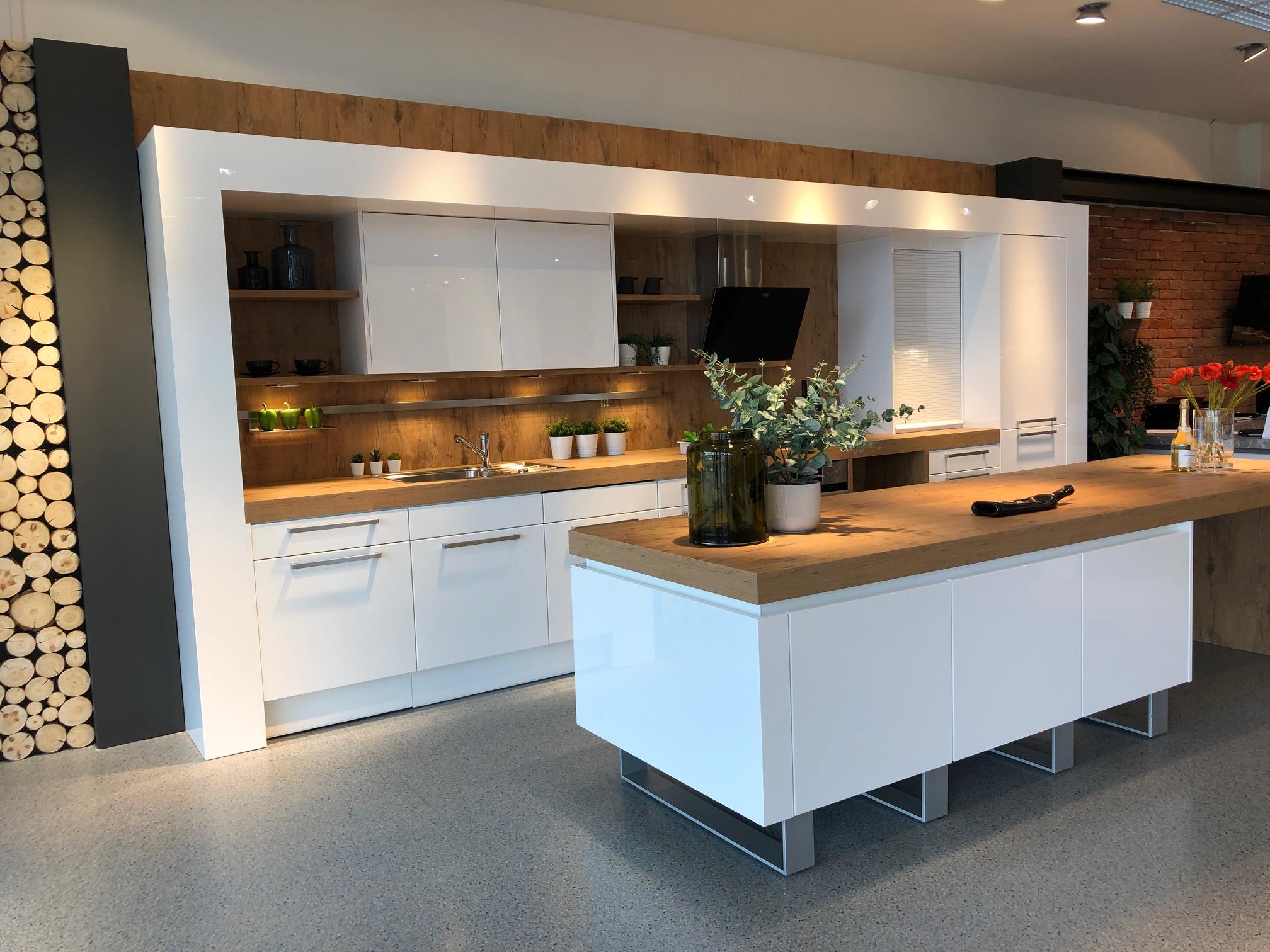 DAN Küche Modell Living mit Fronten in Hochglanz Weiß und Rückwände sowie Arbeitsplatte in Holzdekor Burguesa Eiche.